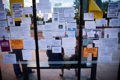 Anuncios de alquiler de pisos y habitaciones para estudiantes en una parada de autobús en Ciudad Universitaria (Madrid).