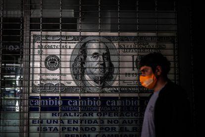 Una persona camina frente a una casa de cambio de divisas, en Buenos Aires.