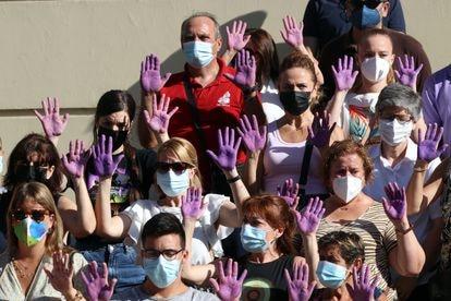 Un grupo de personas con las manos moradas guardan un minuto de silencio en Málaga tras el asesinato machista de una mujer el pasado julio.