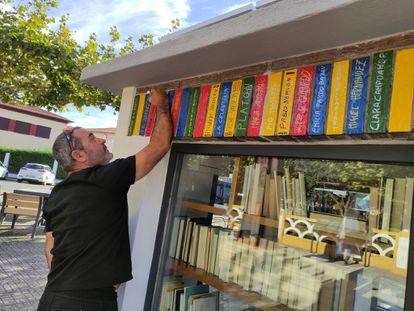 Un vecino escribe el nombre de distintos autores en la bibliocaseta restaurada de Ciudad Rodrigo.