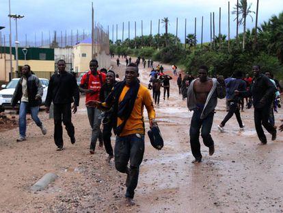 Varios migrantes, tras saltar la valla de Melilla, en una imagen de 2017.