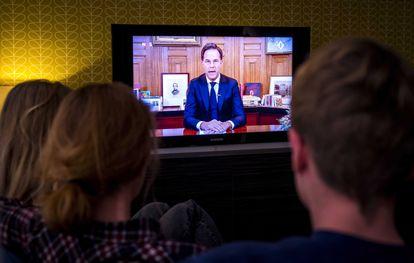 Una familia sigue el discurso del primer ministro de los Países Bajos este lunes.