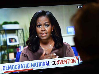 Un hombre mira el discurso de Michelle Obama en la Convención Demócrata.