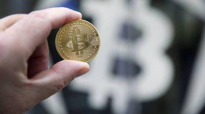 Una moneda de bitcoin sobre el símbolo de la criptodivisa.