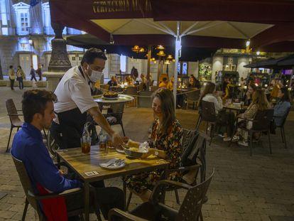 Un camarero sirve a unos turistas en la terraza de la Cervecería Alemana de la plaza de Santa Ana.