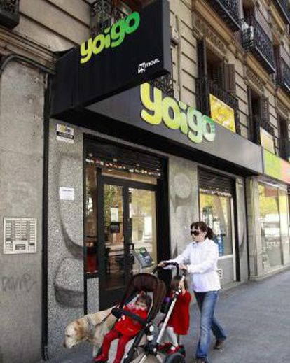 Una mujer y su hijo pasan ante una tienda de Yoigo, en Madrid.