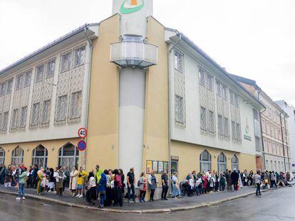 Decenas de personas se concentran este domingo a las afueras del Centro Cultural Islámico de Oslo tras el tiroteo este sábado en una mezquita de la ciudad.