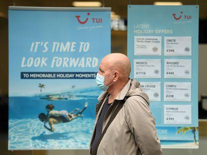 Un hombre con mascarilla pasa ante un anuncio de TUI en Liverpool (Reino Unido), el pasado 2 de octubre,