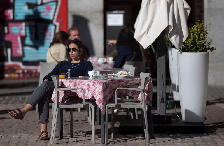Una mujer, al sol, en una terraza del centro de Madrid.