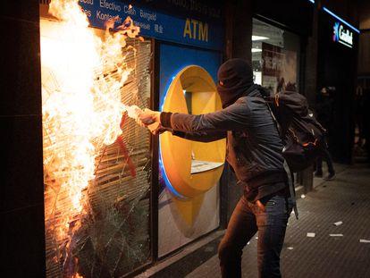 Un encapuchado intenta quemar una sucursal bancaria en Barcelona, el sábado.