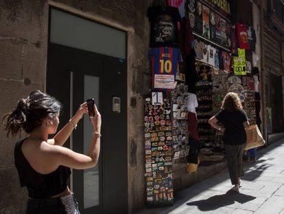 Una mujer hace una foto en una calle de Barcelona.