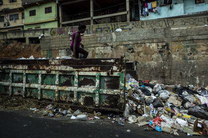 Una vecina del barrio de Petare busca comida en un contenedor de basura en marzo de 2019 en Caracas, Venezuela.