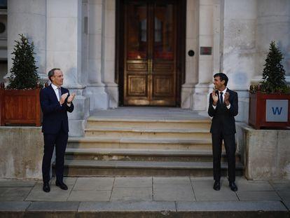 Los ministros de Exteriores, Dominic Raab, y de Economía, Rishi Sunak, aplauden este jueves al personal sanitario