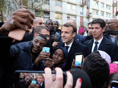El presidente francés, Emmanuel Macron (c), se fotografía con residentes de Clichy-sous-Bois, a las afueras de Paris, este lunes.