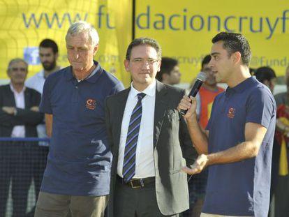 Xavi Hernández, a la derecha, y Cruyff, a la derecha, junto al embajador de la Obra Social La Caixa.