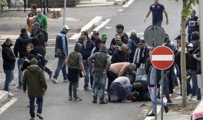 Varios aficionados atienden a un seguidor del Nápoles herido por un disparo.