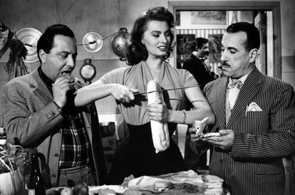 Sophia Loren muestra cómo cortar una rebanada de pan a Peppino De Filippo y Leopoldo Trieste en la película 'El signo de Venus' (1955).