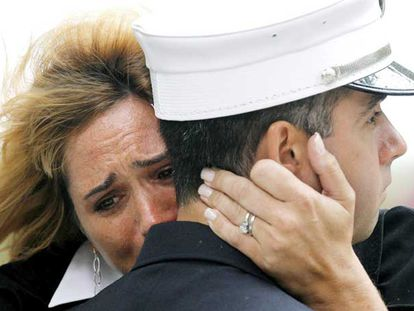 Una mujer llora abrazada a un bombero en Nueva York, durante la ceremonia por el sexto aniversario del 11-S.