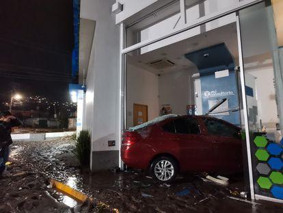 Una persona fotografía un coche arrastrado por la corriente que ha impactado contra un edificio después de las inundaciones de este martes en Ecatepec.