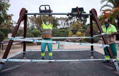 Varios operarios precintan unos columpios en un parque de Valencia el 18 de septiembre.