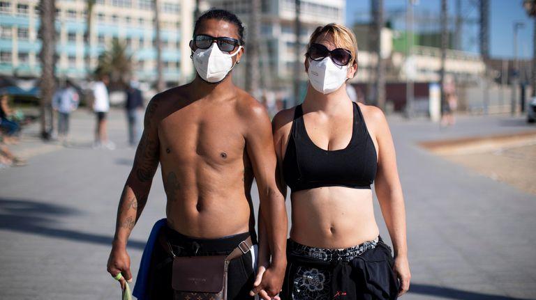 Una pareja con mascarillas practica ejercicio en el litoral de Barcelona.