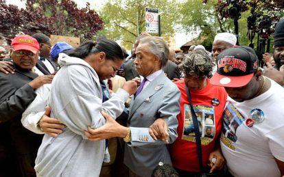 El Reverendo Al Sharpton consuela a la mujer y familiares de Eric Garner, muerto a manos de la policía cuando era detenido en Nueva York.