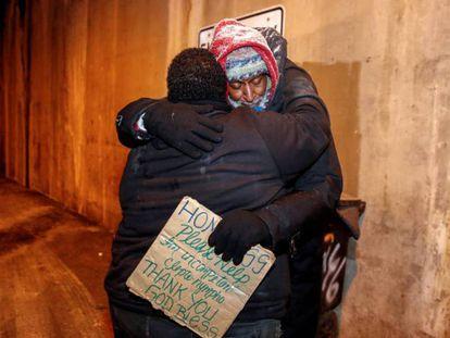 Richard S. Vargas, del departamento de servicios sociales, abraza a Alvin Henry, que vive en la calle. En vídeo, cuando te asas en Australia y te congelas en EE UU.