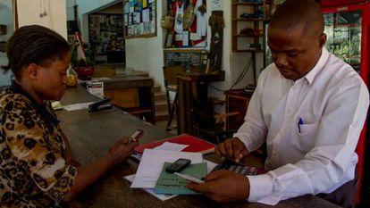 Emma, que tiene un puesto de verduras, hace cuentas a través de M-Pesa con Stephen, responsable de un hotel en Kilifi (Kenia).