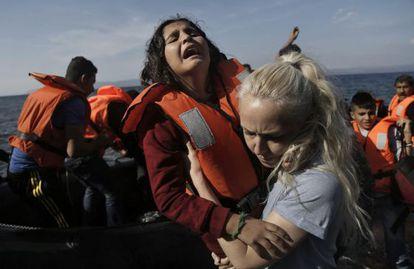 Una niña siria llora mientras es ayudada por una voluntaria a su llegada en lancha a la isla de Lesbos