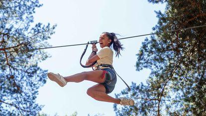 Una adolescente disfruta de una tirolina en un campamento organizado por el Gobierno regional.