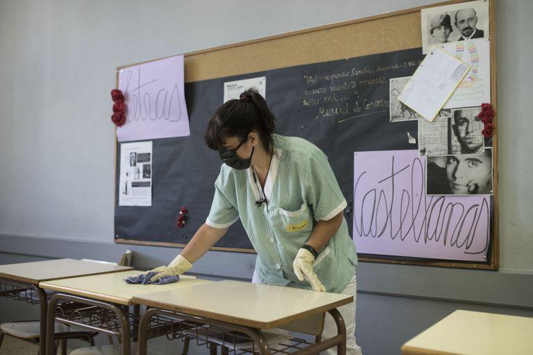 Una trabajadora limpia una aula de un instituto de Barcelona.