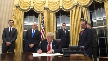 Donald Trump firma en el Despacho Oval frente a las nuevas cortinas doradas.