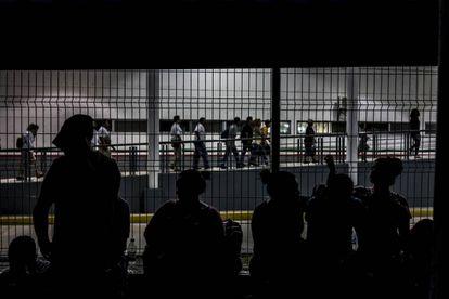 Migrantes centroamericanos esperan en el puente fronterizo la entrega de sus visas humanitarias.