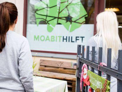 Las fundadoras de la ONG Moabit Hulft ante la sede de su organización en Berlín, fotografiadas de espalda por las amenazas de neonazis recibidas.