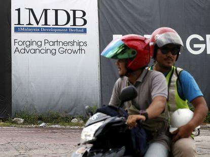 Dos hombres pasan en moto frente a un cartel del fondo soberano 1MDB, en febrero de 2016 en Kuala Lumpur (Malasia).