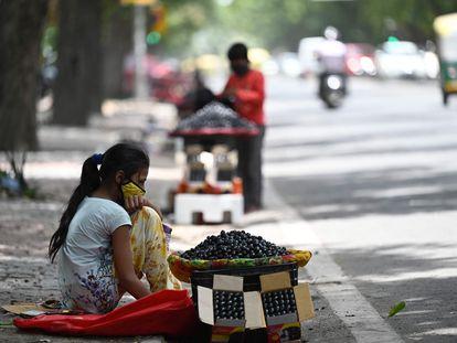 Una niña vende ciruelas en un puesto de carretera en Nueva Delhi, el pasado 30 de junio de 2021.