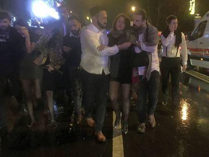 Un grupo de jóvenes abandonan la discoteca después del ataque.