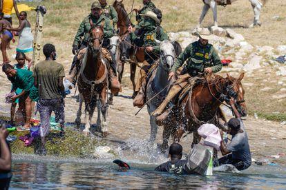 Agentes de frontera de EE UU intentan detener a un grupo de migrantes haitianos.