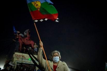 """Una mujer con la bandera mapuche en la celebración de triunfo del """"apruebo"""" para escribir una nueva Constitución en Chile."""