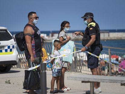 Un agente de la Guardia Urbana cierra los accesos a la playa de Barcelona este sábado.