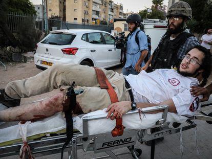 Fuerzas de seguridad israelíes trasladan a un judío herido por disparos en las protestas del jueves en la ciudad de Lod.