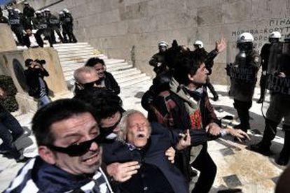 Manolis Glezos es auxiliado tras ser golpeado por la policía durante una protesta en marzo de 2010 en Atenas