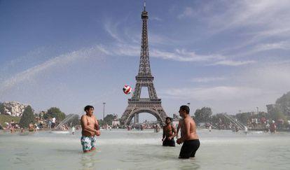 Jóvenes junto a la Torre Eiffel durante la ola de calor de la semana pasada.