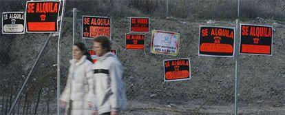 Una pareja pasea ante una valla con carteles de pisos en venta y en alquiler en Madrid.