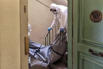 Empleados de los servicios funerarios transportan el cuerpo  de J.E.D.,  fallecido en el barrio de Gracia de Barcelona.