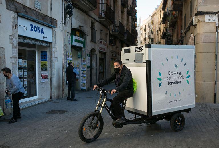 Un repartidor distribuye pan congelado para supermercados de Ciutat Vella con una bicicleta de carga eléctrica.