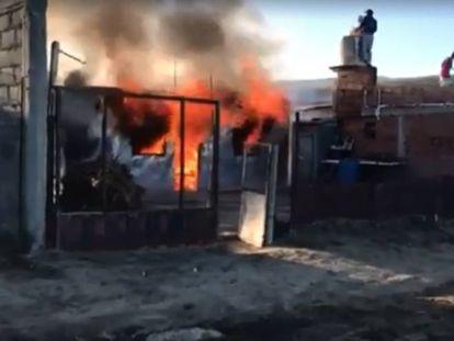 La casa en llamas del padre del hombre acusado falsamente de violador, en un barrio de la periferia de Comodoro Rivadavia, Chubut, Argentina.