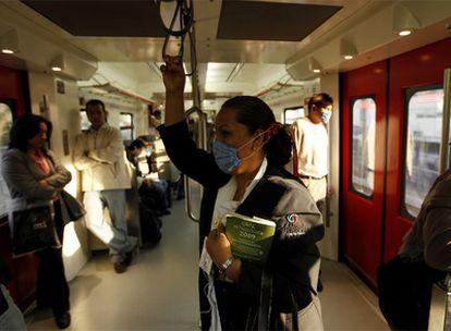 Una mujer viaja en un tren de Ciudad de México ataviada con mascarilla por el brote del extraño virus de gripe que afecta al país.