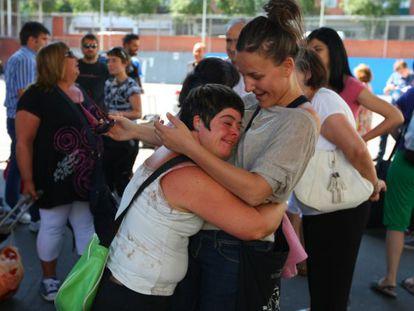 Una participante en el programa de vacaciones se abraza a una de las monitoras.
