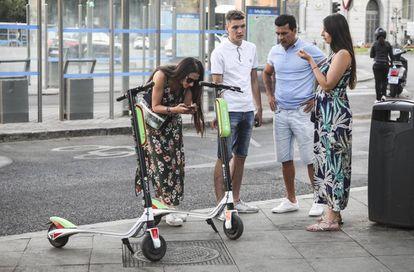Varias personas observan los nuevos patinetes eléctricos de la empresa de alquiler Lime, en la plaza de Cibeles.